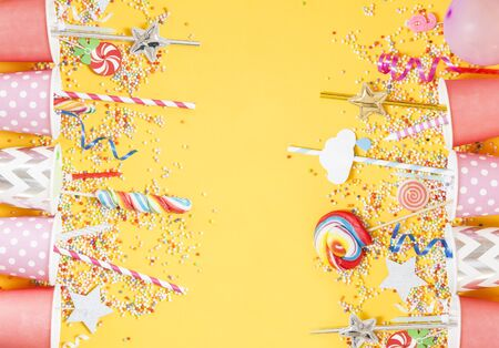 Birthday candies and accessory on yellow background