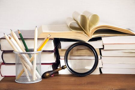 Books and the magnifying glass on wooden background