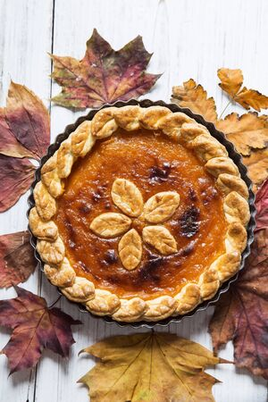 Pumpkin pie with the dry autumn leaves