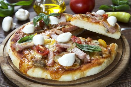 Rustic homemade pizza on wooden board 写真素材