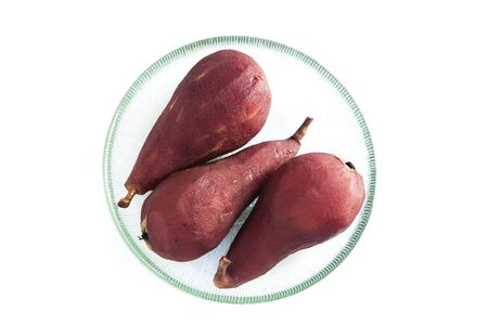Poached pears in red wine on a plate
