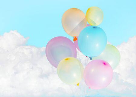 Kleurrijke ballonnen boven witte wolken Stockfoto