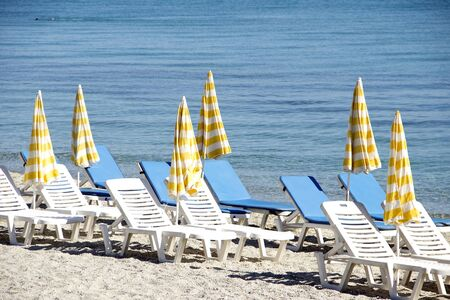 Vacant beach with yellow umbrellas and deckchairs