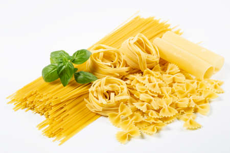 Various pasta with basil on white background
