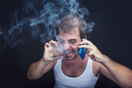Angry man smoking a cigar and shouting on the phone, dressed in undershirt, rude and unpleasant