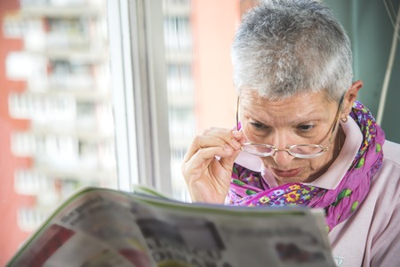 Senior elderly lady having troubles with her eye glasses, cant see well and cant read the small letters in the newspapers Stockfoto
