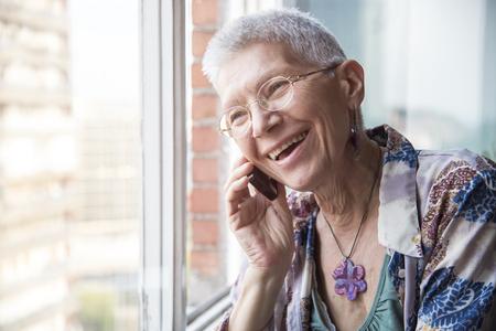 Smiling senior elderly lady having a pleasant conversation over her phone Archivio Fotografico
