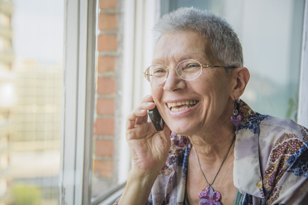 Smiling senior elderly lady having a pleasant conversation over her phone Stock Photo