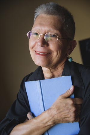 Senior woman holding her favorite book, remembering old love