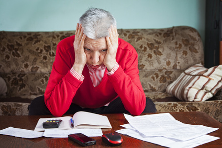 Senior old woman desperate over the bills she has to pay, worried and with headache Stock Photo