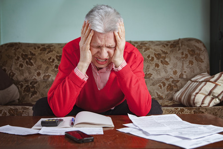 Senior old woman desperate over the bills she has to pay, worried and with headache 版權商用圖片