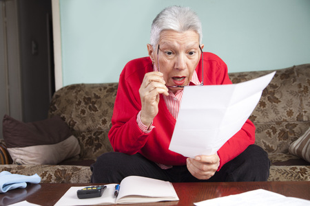 Senior old woman shocked with the bills she receives, appalled and gasping Banque d'images - 94189656