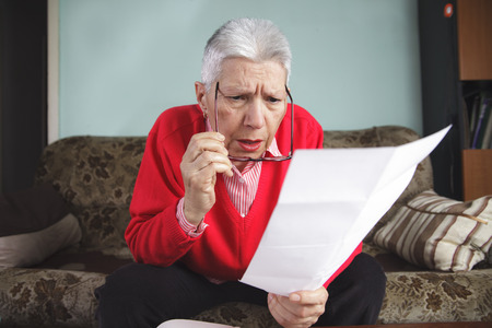 Senior old woman shocked with the bills she receives, appalled and gasping Stock Photo