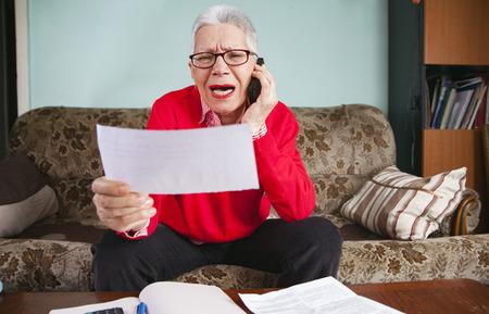 Haute femme âgée hurlant contre sa banque, en colère contre le montant de ses factures, discutant avec un agent du service clientèle