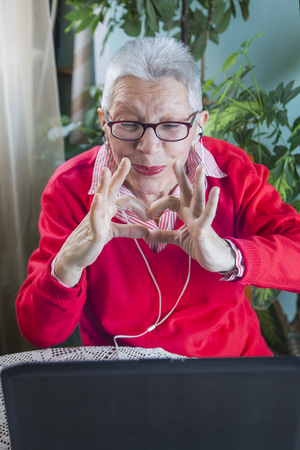 Senior old woman sending love and kisses to her family over social media apps using her laptop
