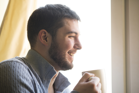 Young bearded holding a ceramic cup. enjoying the smell of his morning coffee or tea, looking out the window Фото со стока