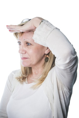 Senior blonde lady looking away to a distant spot, eyesight health or hope concept Stock Photo