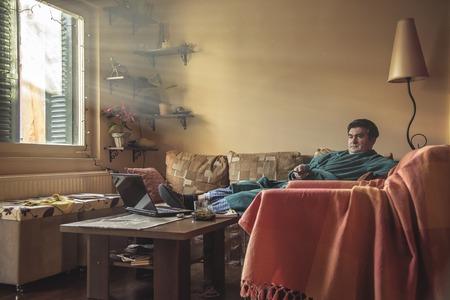 Mature man watching tv in his living room, dressed in bathrobe