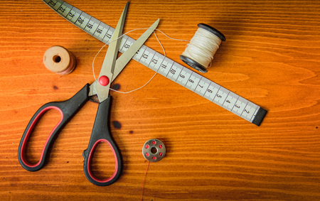 Clothing tools and accessories, scissors, measuring tape, and a roll of thread