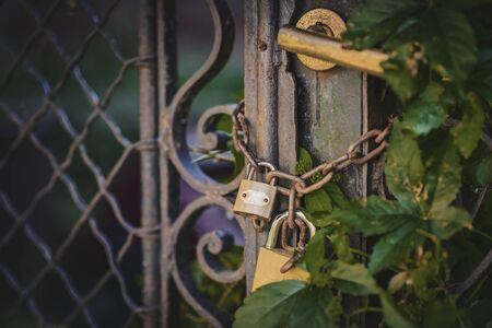 Two golden padlocks on a rusty chain guarding the entrance through an aged gate, closeup image Stock Photo