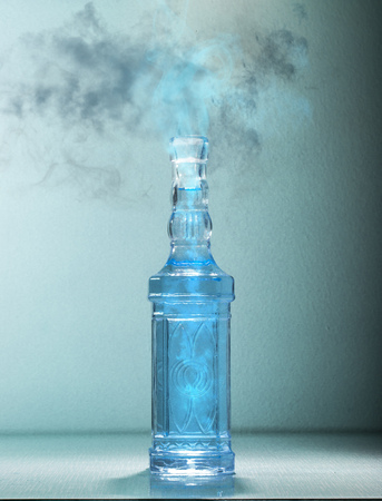 Blue magic potion releasing smoke and fume from a bottle Stock Photo
