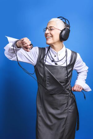 Senior old woman listening to her favorite music through big headphones, enjoying the rich sound Stock Photo