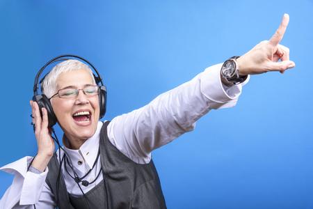 Senior old woman listening to her favorite music through big headphones, enjoying the rich sound 版權商用圖片