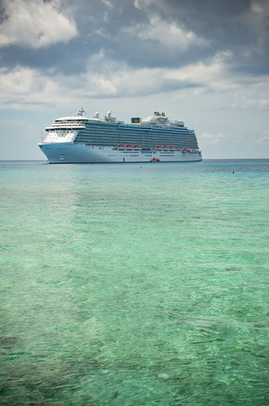 MARCH, 2015 - ST. THOMAS, CARIBBEAN: Big cruise ship docked in the middle of the ocean on the clear water, dramatic sky and sun