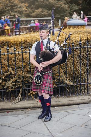 AUGUST 2013, EDINBURGH SCOTLAND: Bagpipe player entertaining passersby on a street in Edinburgh