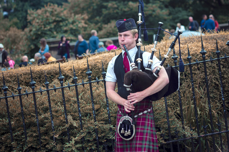 AUGUST 2013, EDINBURGH SCOTLAND: Bagpipe player entertaining passersby on a street in Edinburgh Editorial