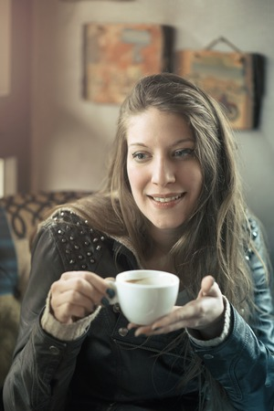 Cheerful young casual lady drinking her coffee in a coffee shop, enjoying some free time for herself Stock Photo
