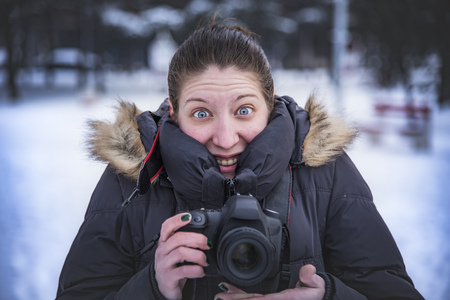 Funny young woman holding a professional dslr camera on a cold winters day