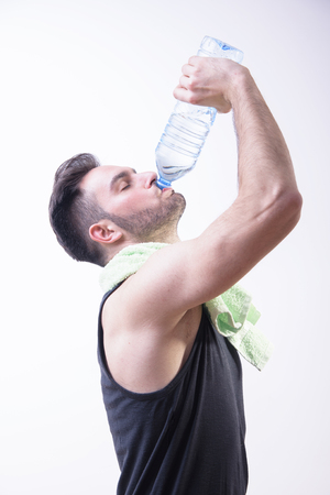 Atheltic sporty man drinking water from a bottle after some hard training