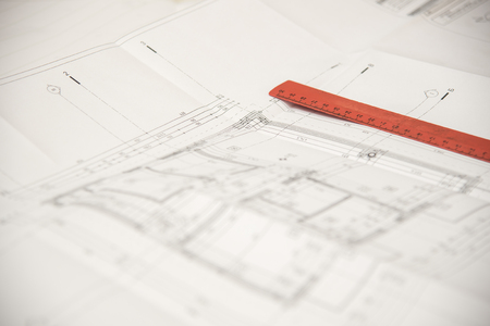Red ruler on top of a paper blueprint for a certain construction or a building