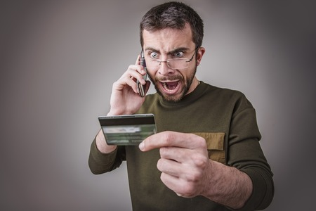 Angry young man having an argument with his bank for the credit card bill he received Stock Photo