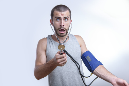 Young man shocked and surprised by his blood pressure results Stock Photo