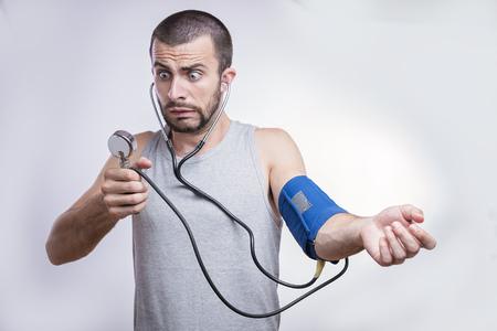 Młody człowiek zszokowany i zaskoczony wynikami jego ciśnienia krwi