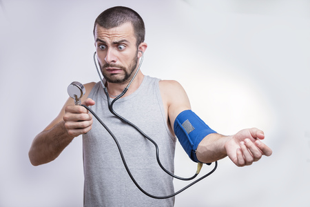 Young man shocked and surprised by his blood pressure results Banque d'images