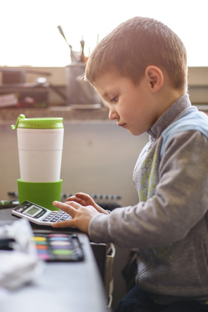 Cute little toddler boy using a calculator, figuring out a math problem, developing logic skills Stock Photo