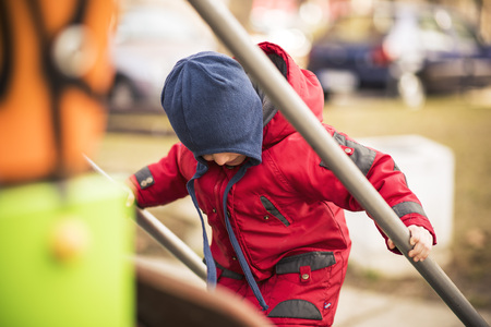 Cute little boy toddler climbing the children fort in the playground, having fun