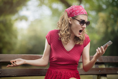 Young woman dressed in vintage red dress having a shocking and surprising phone call, overreacting to some bad news Stock Photo