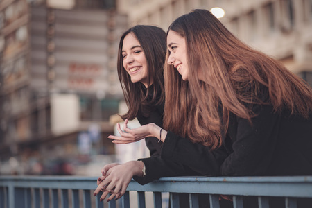 Two beautiful girls on the street having a small chat, enjoying a walk