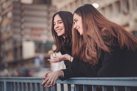 Zwei schöne Mädchen auf der Straße, die ein kleines Schwätzchen, einen Spaziergang genießend haben Standard-Bild