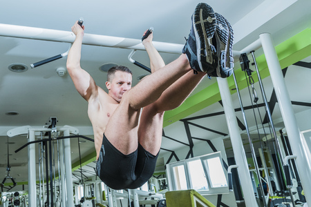 Strong man exercising in the gym on pull up bar, raised legs exercise
