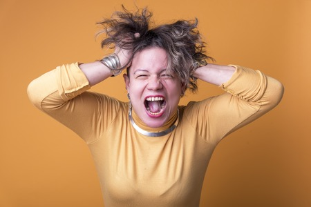 Furious and enraged young woman screaming with anger, yellow background Stock Photo