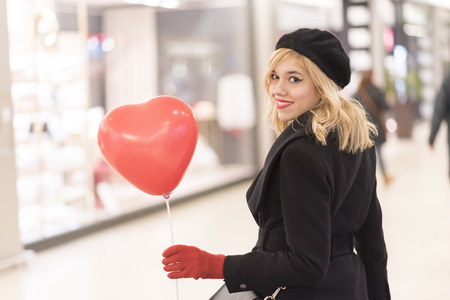 Beautiful blonde woman in a coat walking in the shopping mall, holding a heat shaped umbrella, valentines day Stok Fotoğraf