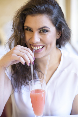 Young beautiful woman drinking a grapefruit juice using a straw, sitting in a well lit cafe Stock Photo