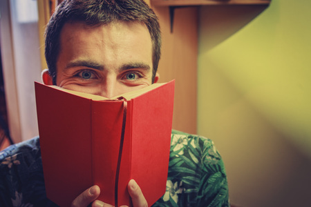 Young man holding a book up to his face, smelling the pages
