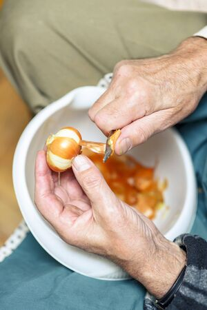 Senior elderly man peeling onion skin with a small sharp knife, preparing ingredients for lunch