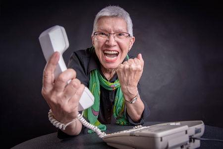 Angry, enraged senior woman yelling at a landline office phone, unhappy with customer service provided by the agent on the other side Imagens